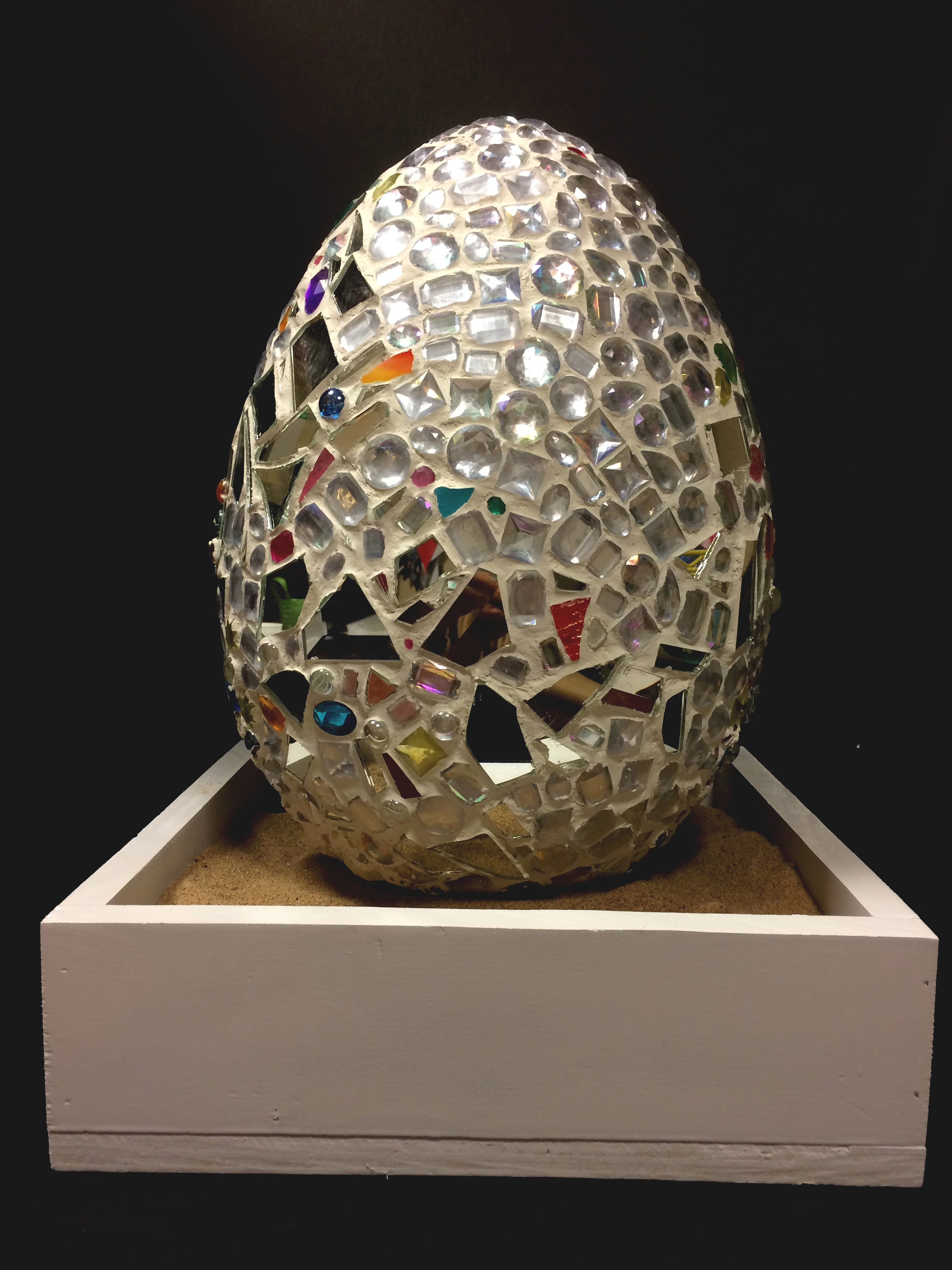 A large grey and colorful mosaic egg