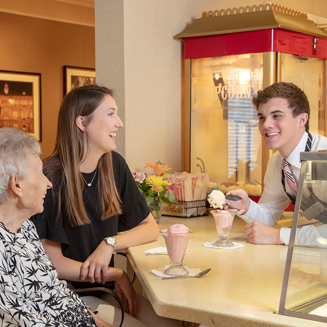 A young woman and an older woman enjoying a drink with a male service worker