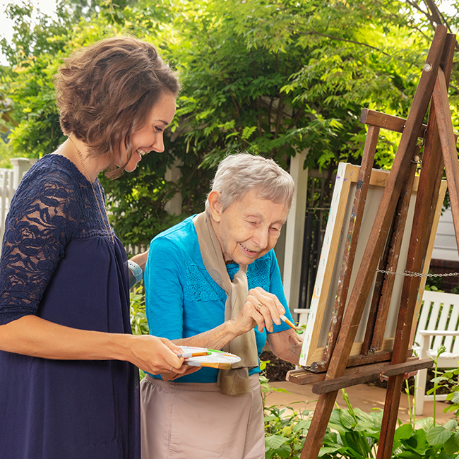 A young woman painting outside with an older woman