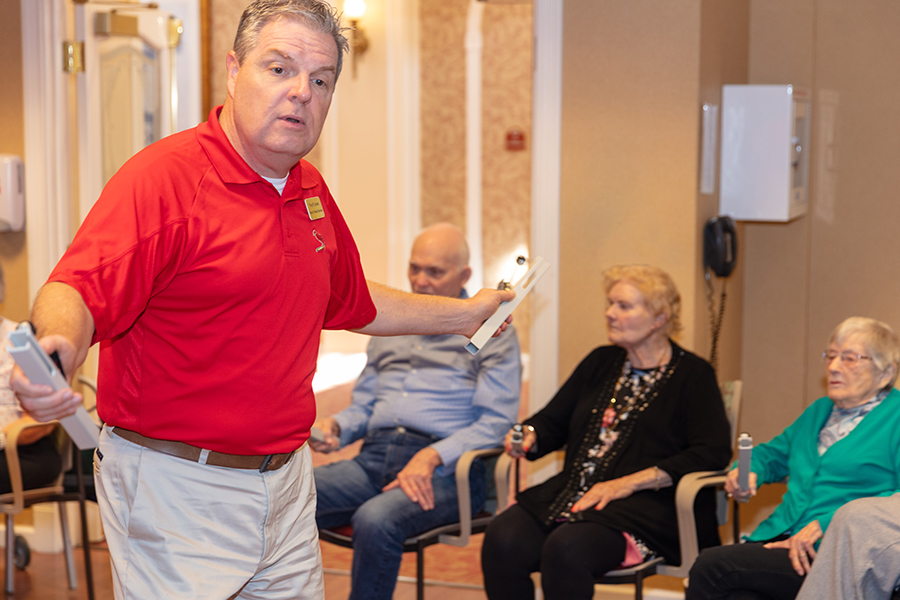 Musical Therapist in Red Polo leading residents in activity