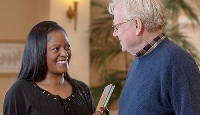 A smiling woman having a conversation with a man