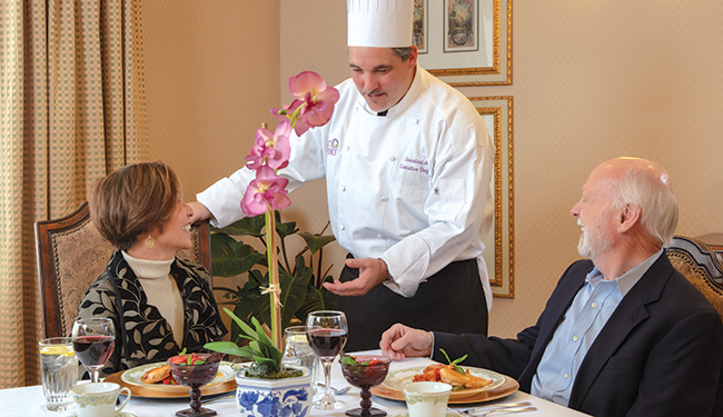 A chef talking to two people while having they enjoy dinner and drinks