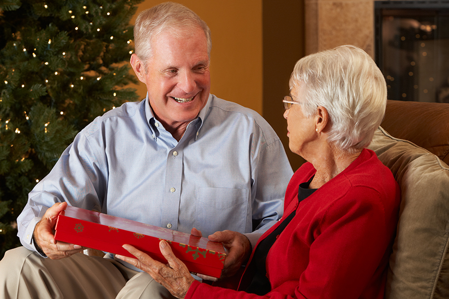 A man and a woman sit on a couch exchanging a holiday gift