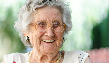 Senior woman sitting outside and laughing.