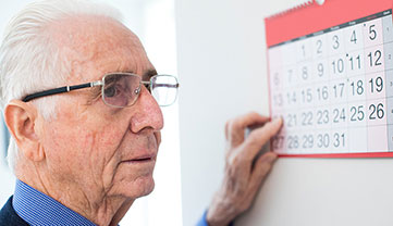 A man pointing to a day on a calendar.