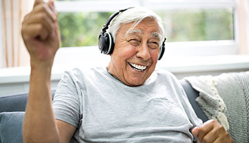 A man smiling with headphones on